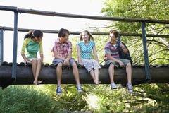 Adolescentes que sentam-se na ponte de madeira Fotografia de Stock