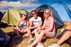 Adolescentes que sentam-se na terra na frente das barracas Imagem de Stock Royalty Free