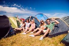 Adolescentes que sentam-se na terra na frente das barracas Imagens de Stock Royalty Free