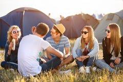 Adolescentes que sentam-se na terra na frente das barracas, comendo Foto de Stock