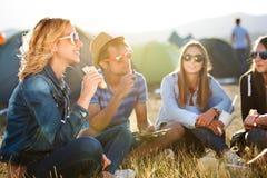 Adolescentes que sentam-se na terra na frente das barracas e de comer Fotos de Stock