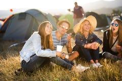 Adolescentes que sentam-se na terra na frente das barracas e de comer Imagens de Stock Royalty Free