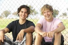 Adolescentes que sentam-se no campo de jogos Foto de Stock