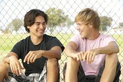 Adolescentes que sentam-se no campo de jogos Imagem de Stock Royalty Free