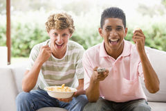 Adolescentes que sentam-se no sofá que come batatas fritas Fotografia de Stock