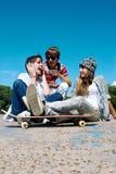 Adolescentes que sentam-se por uma rua Fotos de Stock