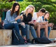 Adolescentes que sientan y que miran sus teléfonos móviles Imágenes de archivo libres de regalías