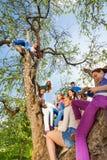 Adolescentes que sientan y que sostienen móviles en el árbol Fotografía de archivo