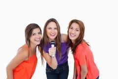 Adolescentes que sonríen mientras que canta un Karaoke Imagen de archivo