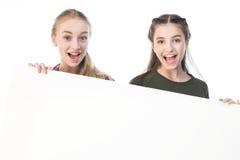 Adolescentes que sostienen la bandera en blanco aislada en blanco Imagenes de archivo