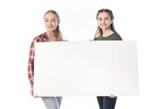 Adolescentes que sostienen la bandera en blanco aislada en blanco Fotos de archivo libres de regalías