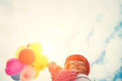 Adolescentes que sostienen los globos coloridos en la playa con el bl Imagen de archivo libre de regalías