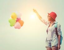 Adolescentes que sostienen los globos coloridos mochila azul que lleva Fotos de archivo