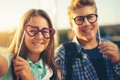 Adolescentes que sostienen los vidrios felices Imagen de archivo libre de regalías