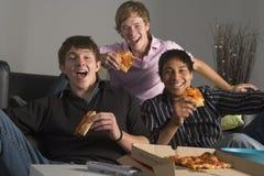 Adolescentes que têm o divertimento e que comem a pizza Imagem de Stock