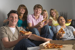 Adolescentes que têm o divertimento e que comem a pizza Fotos de Stock Royalty Free