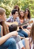 Adolescentes que tocan la guitarra y que cantan Imagen de archivo libre de regalías