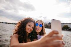 Adolescentes que toman el selfie con el teléfono elegante por el lago Foto de archivo libre de regalías