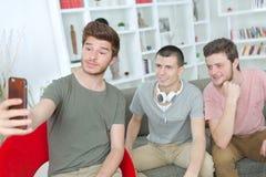 Adolescentes que toman el selfie con el teléfono móvil en sala de estar Imágenes de archivo libres de regalías