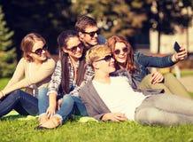 Adolescentes que toman la foto afuera con smartphone Fotografía de archivo libre de regalías