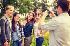 Adolescentes que toman la foto con la cámara digital afuera Foto de archivo