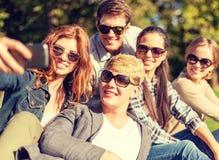 Adolescentes que toman la foto con smartphone afuera Foto de archivo
