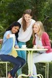 Adolescentes que toman la foto en el teléfono móvil en el café al aire libre Imagen de archivo