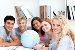 Adolescentes que trabajan con un globo terrestre Foto de archivo libre de regalías