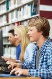 Adolescentes que trabajan en los ordenadores en biblioteca Imagenes de archivo