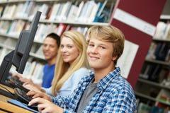 Adolescentes que trabajan en los ordenadores en biblioteca Imagen de archivo