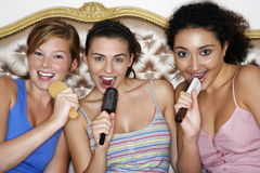 Adolescentes que usan cepillos como micrófonos Imagen de archivo