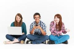 Adolescentes que usan diversas formas de tecnología de Digitaces en estudio Foto de archivo