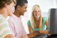 Adolescentes que usan la computadora de escritorio Imágenes de archivo libres de regalías