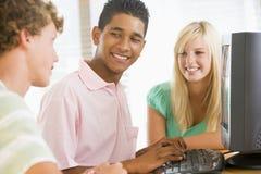 Adolescentes que usan la computadora de escritorio Fotos de archivo