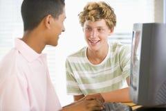 Adolescentes que usan la computadora de escritorio junto Foto de archivo