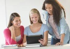Adolescentes que usan la tableta de Digitaces junto en sala de clase Fotos de archivo libres de regalías