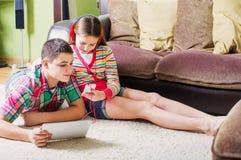 adolescentes que usan la tableta electrónica y el teléfono móvil Imagen de archivo