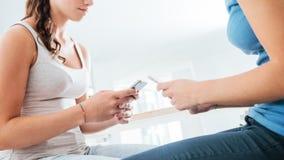 Adolescentes que usan los teléfonos elegantes Fotografía de archivo libre de regalías