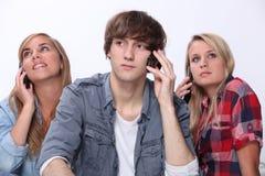 Adolescentes que usan los teléfonos móviles Foto de archivo