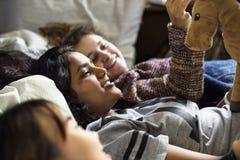 Adolescentes que usan smartphones en Internet de la cama en fiesta de pijamas Imagen de archivo