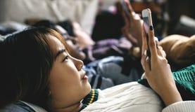 Adolescentes que usan smartphones en una cama Imagen de archivo libre de regalías
