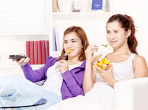 Adolescentes que ven la TV y que comen la ensalada de fruta Foto de archivo