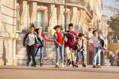Adolescentes rollerblading a lo largo de las calles de la ciudad Imagenes de archivo