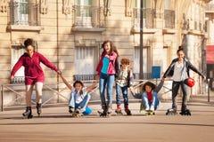 Adolescentes rollerblading y que andan en monopatín junto Fotografía de archivo libre de regalías