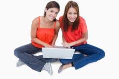 Adolescentes s'asseyant avec un ordinateur portable sur des pattes Image libre de droits