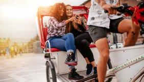 Adolescentes s'asseyant sur le tricycle utilisant le téléphone portable Photographie stock