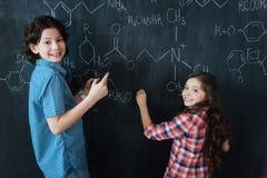 Adolescentes satisfechos que disfrutan de la clase de química en la escuela Imágenes de archivo libres de regalías