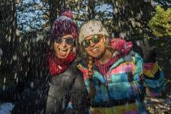 Adolescentes sonrientes bajo caída de la nieve que lleva la ropa caliente y s Imágenes de archivo libres de regalías