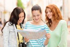 Adolescentes sonrientes con el mapa y la cámara Imágenes de archivo libres de regalías