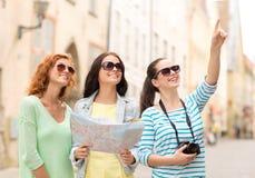 Adolescentes sonrientes con el mapa y la cámara Foto de archivo